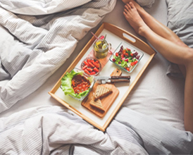 a woman laying in bed eating lunch