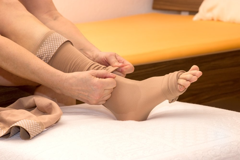 a person putting compression stockings on their leg