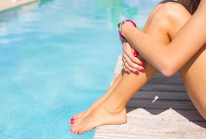 a woman with smooth, healthy legs sitting by a pool